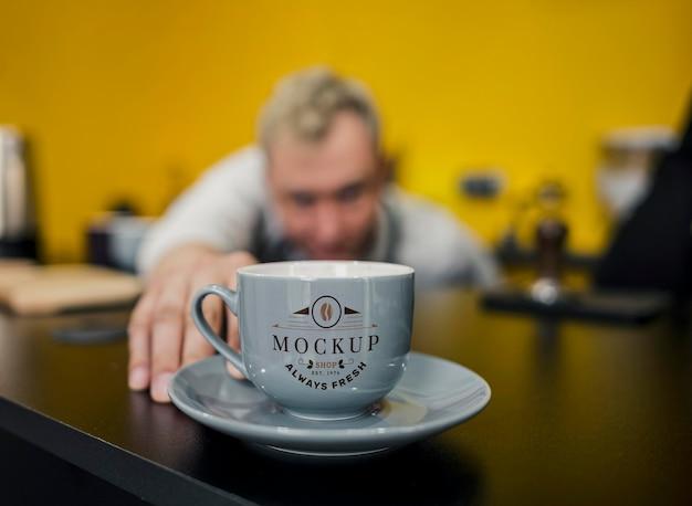 Бариста расставляет макет кофейной кружки Premium Psd