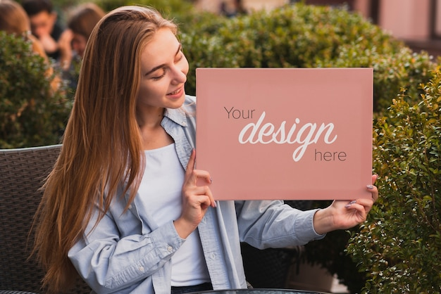 Beautiful girl holding a banner mock-up Free Psd