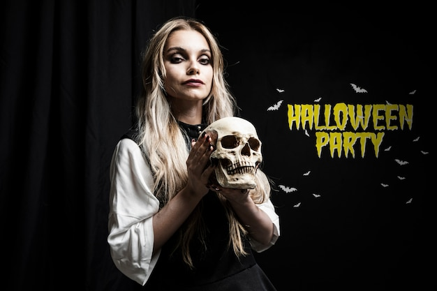 Beautiful scary woman with blonde hair holding a skull Free Psd