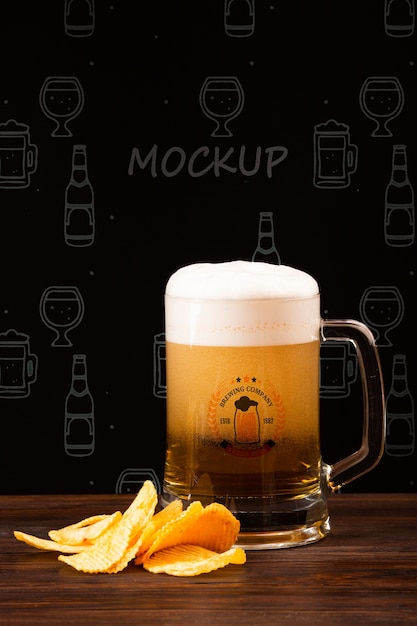 Beer mug with foam and chips beside Free Psd