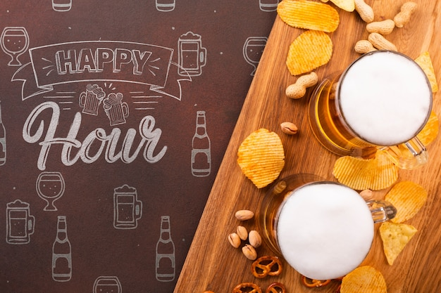 Beer mugs on wooden tray with chips Free Psd