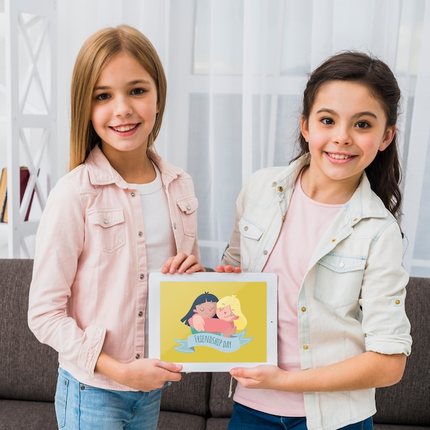 Best friends holding a tablet together mock-up Free Psd