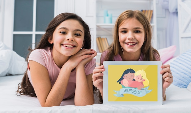 Best friends smiling while looking at the camera with tablet mock-up Free Psd