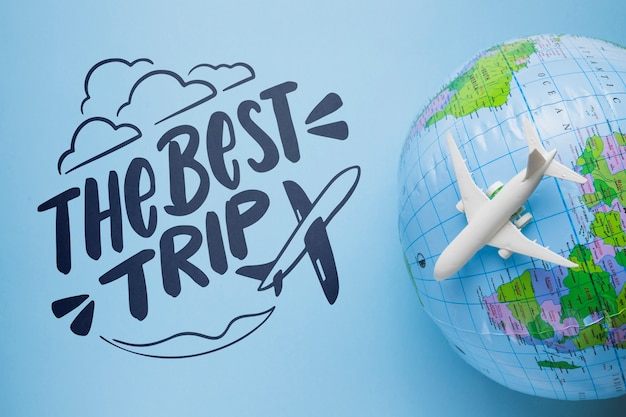 The best trip lettering with earth globe and airplane toy Free Psd