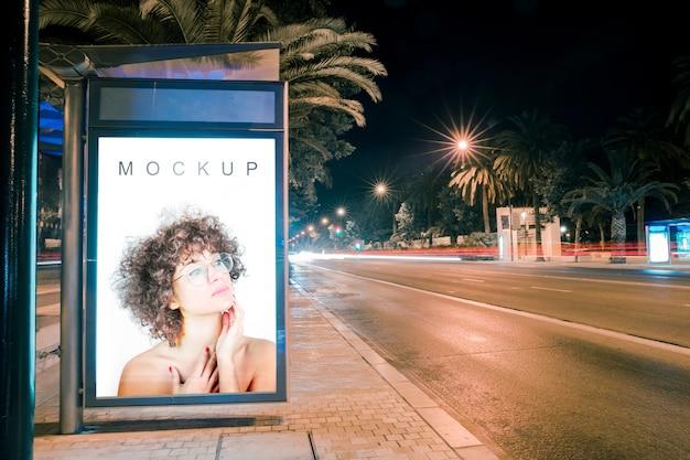 Billboard mockup at bus stop at night Free Psd
