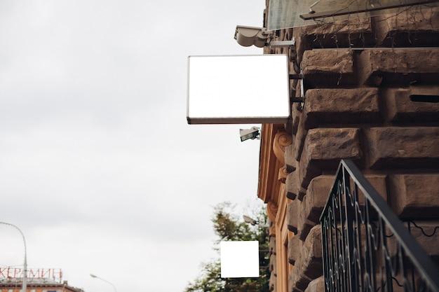 Un tabellone per le affissioni, modello, dal lato di un edificio fuori contro un bel cielo blu Psd Gratuite