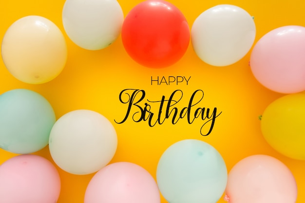 Birthday background with colorful balloons on yellow Free Psd