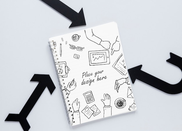 Black arrows and notebook with doodles Free Psd