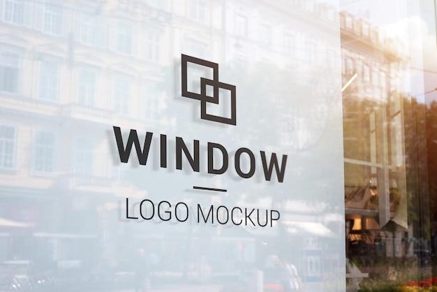 Черный логотип макет на витрине с белым крытый. современная витрина в центре города. здания и солнечный свет в отражении Premium Psd