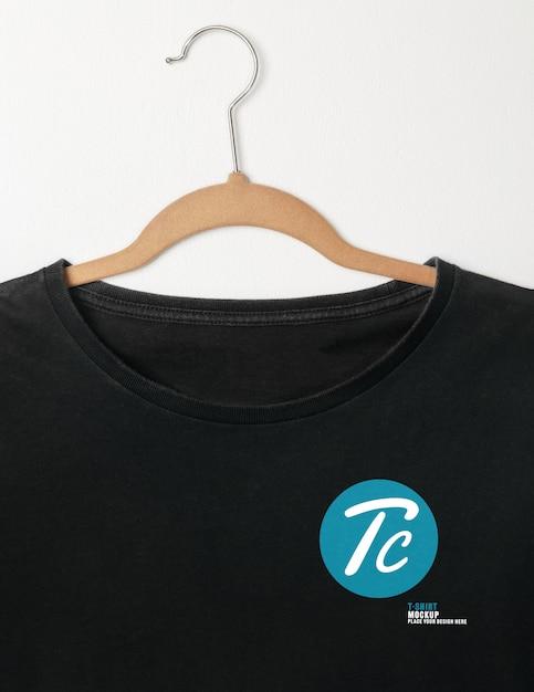 Blank black t-shirts mockup hanging on white wall Premium Psd