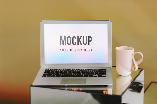 Blank laptop screen and a pink coffee cup Free Psd