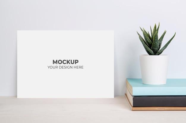 木製のテーブルの上の本に鉢植えの空白のモックアップ紙シートと植物 Premium Psd