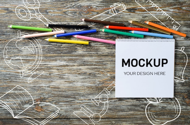 空白のノートブックと木製のテーブルにカラフルな鉛筆のセット。用紙の背景。モックアップ。バナー。上からの眺め Premium Psd