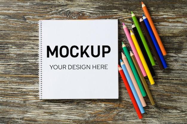 空白のノートブックと木製のテーブルにカラフルな鉛筆のセット。用紙の背景。モックアップ。上からの眺め Premium Psd