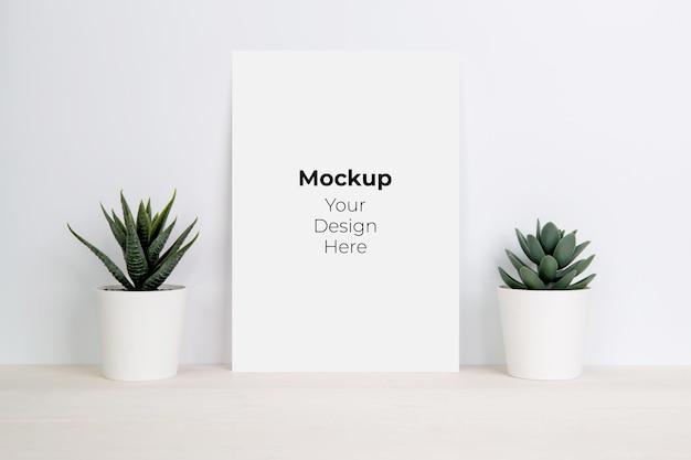 木製のテーブルに鉢植えのモックアップと植物の空白の紙シート Premium Psd