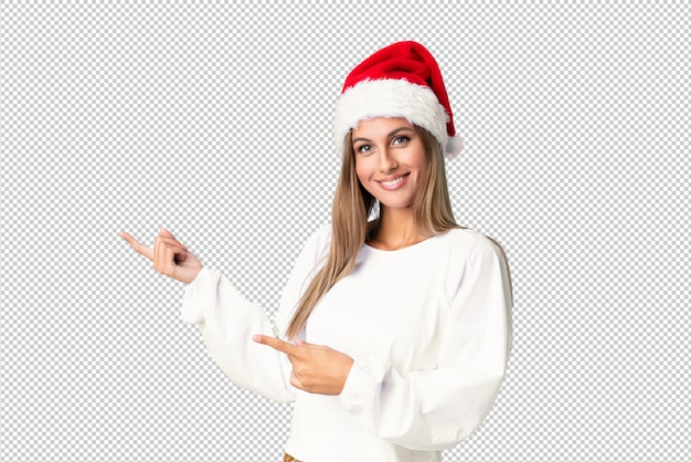 Blonde girl with christmas hat pointing finger to the side Premium Psd