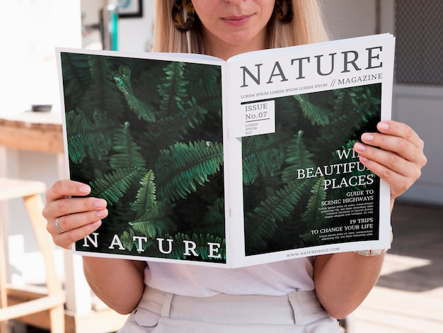 Blonde woman looking into a nature magazine mock up Free Psd