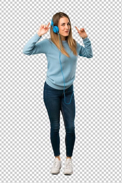 Blonde woman with blue shirt listening to music with headphones and dancing Premium Psd