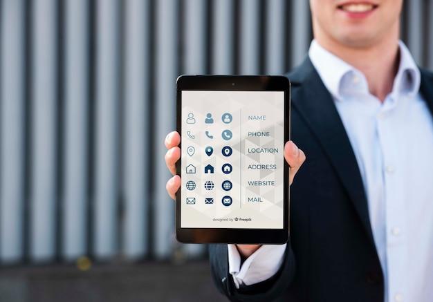 Затуманенное мужчина держит цифровой планшет на открытом воздухе Бесплатные Psd
