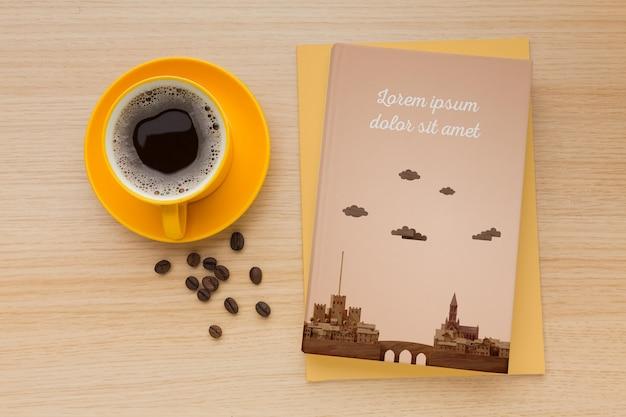 커피 한잔과 함께 나무 배경에 책 표지 구색 무료 PSD 파일