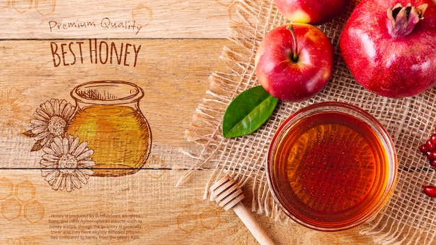 Bowl with honey beside apples Free Psd