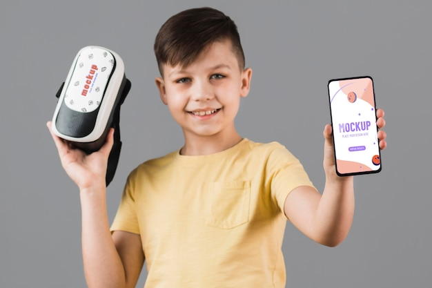 Boy holding virtual reality headset with phone mock-up Free Psd