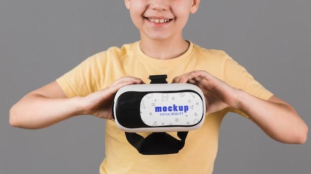 Boy holding virtual reality headset Free Psd