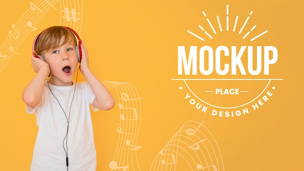 Boy listening to music through headphones with background mock-up Free Psd