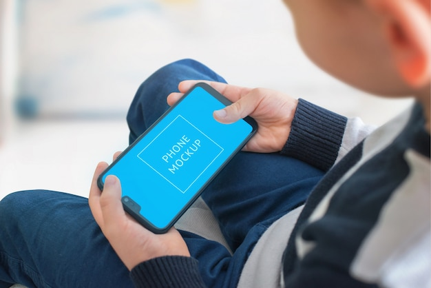 Boy play game on smart phone concept. smart object screen for app, game presentation mockup. Premium Psd