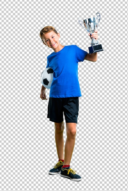 Boy playing soccer and holding a trophy Premium Psd