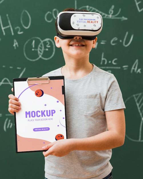 Boy wearing virtual reality headset with clipboard mock-up Free Psd