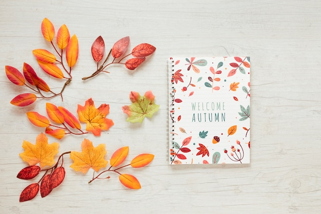 Branches of dried leaves and notepad Free Psd