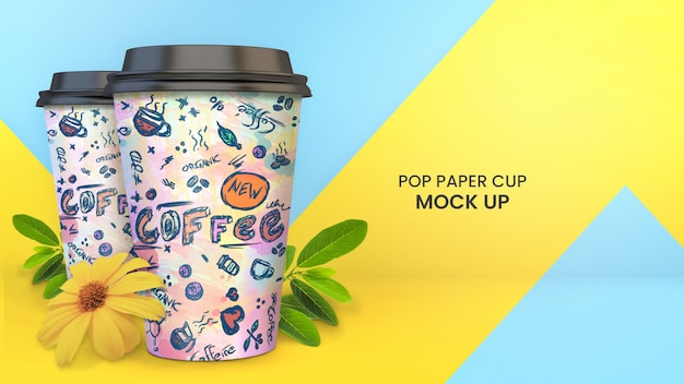 Bright and colorful paper cup mockup of two paper coffee cups with plants, foliage, and yellow flowers Premium Psd