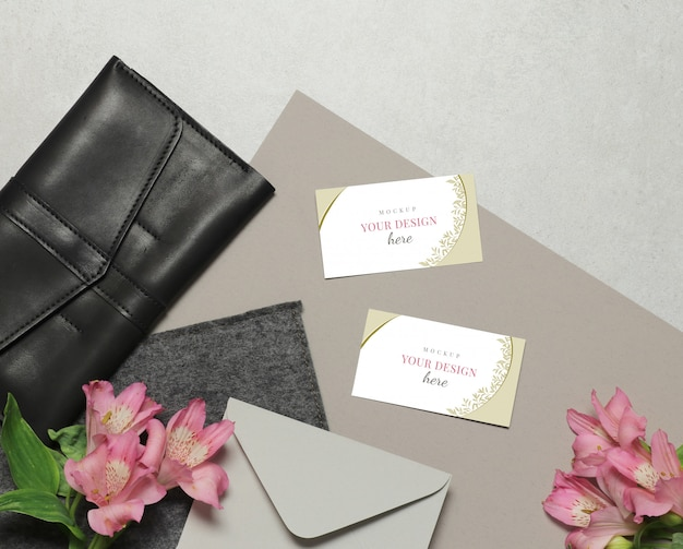 Business card on grey background with flowers, envelope and purse Premium Psd
