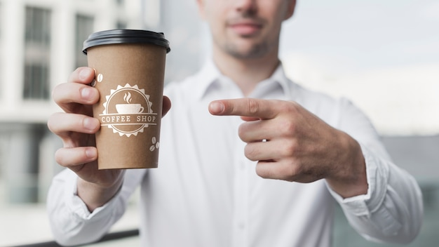 Business man pointing at a coffee cup mock-up Free Psd