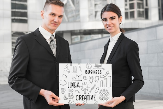 Business people holding paper mockup Free Psd