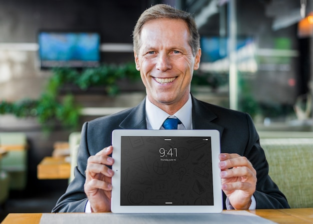 Businessman presenting tablet mockup Free Psd