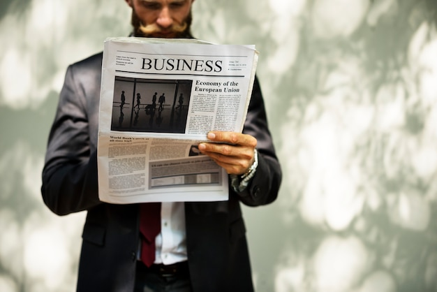 Businessman standing and reading newspaper Free Psd