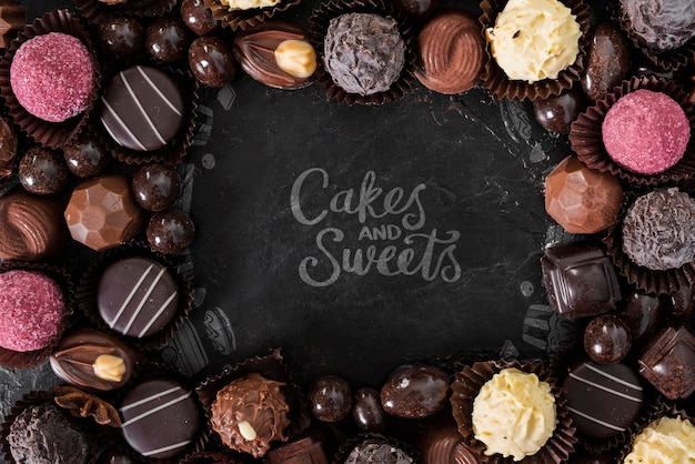 Cakes and sweets surrounded by pralines and candies Free Psd