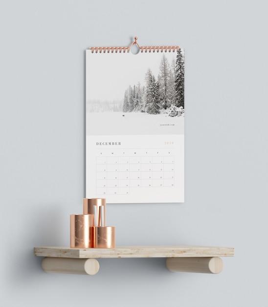 Calendar hookes on wall above shelf mock-up Free Psd