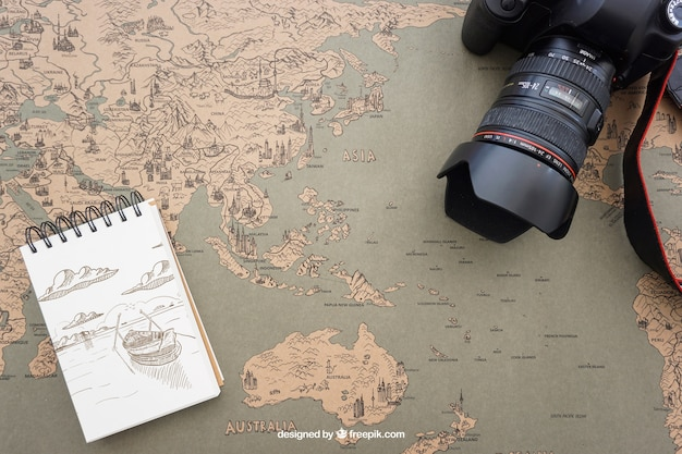 Camera and notepad on world map Free Psd