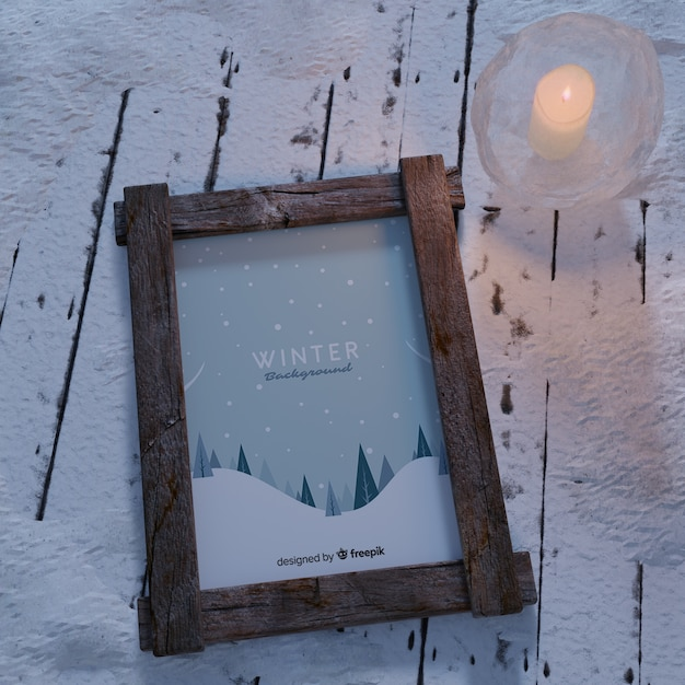 Candle beside frame with winter theme Free Psd