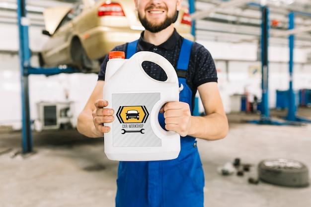 Car mechanic holding plastic can mockup Free Psd