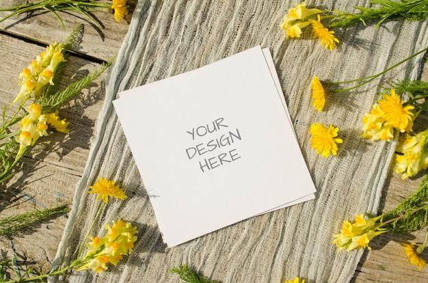 소박한 스타일의 오래 된 나무 배경에 노란색 꽃과 함께 카드 모형 프리미엄 PSD 파일