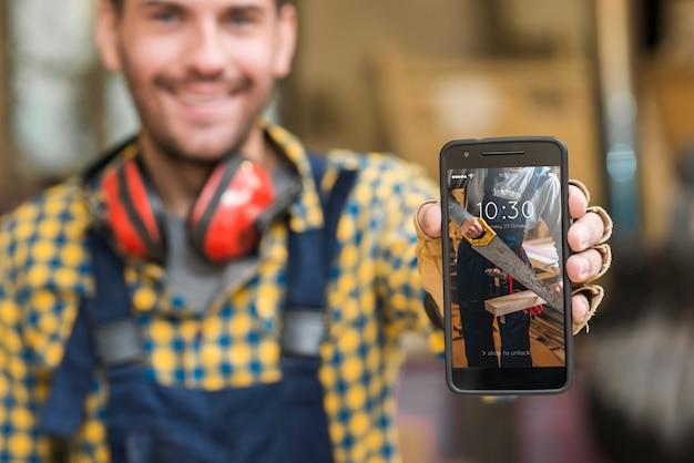 Carpenter che tiene smartphone mockup Psd Gratuite