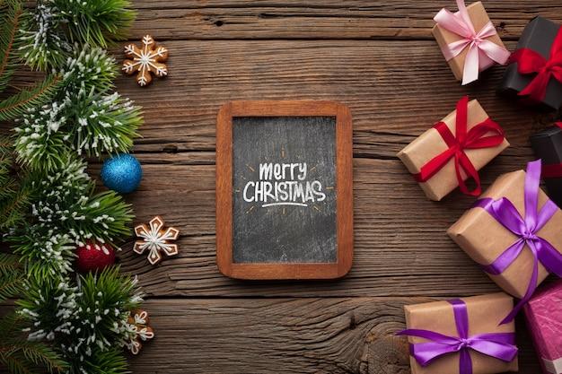 Макет доски и подарки с рождественскими сосновыми листьями Бесплатные Psd