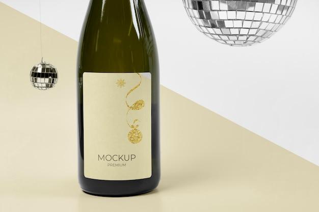 Макет бутылки шампанского и серебряные диско-шары Бесплатные Psd