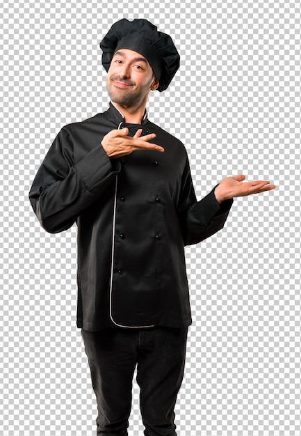 Chef man in black uniform extending hands to the side and smiling for presenting Premium Psd