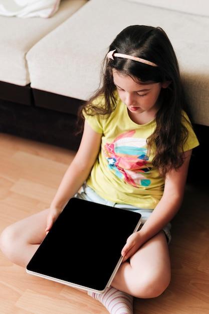 手にデジタルタブレットを持って床に座っている子供 無料 Psd