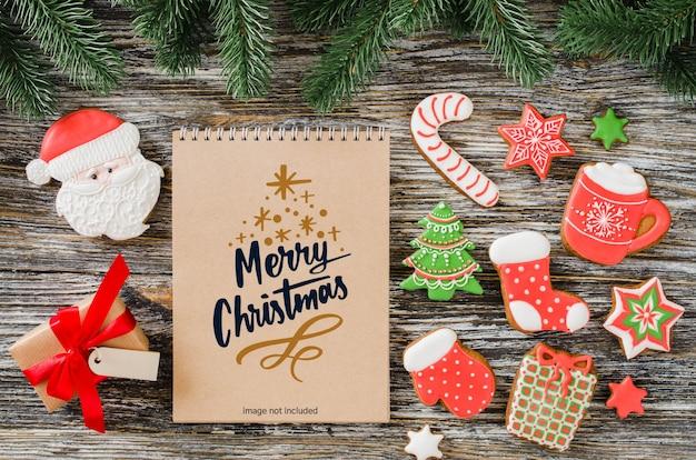 茶色のノートブックモックアップ、ジンジャーブレッドクッキー、モミの木とクリスマスの背景 Premium Psd